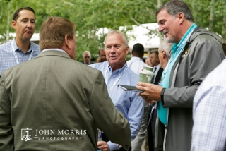 Small group of attendees in casual business attire sharing ideas during an outdoor networking session