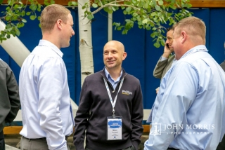 Three business professionals sharing ideas during an outdoor networking event in Aspen, CO.