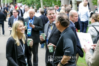 Group of attendees in professional attire sharing coffee and a laugh at a networking event in Aspen, CO.