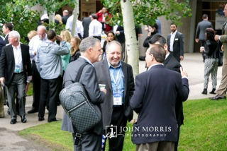 Group of businessmen sharing ideas and a laugh during an outdoor networking event at a conference in Aspen, CO.