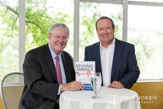Steve Forbes and Executive smiling and posing for the camera during a book signing event.