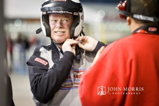 Executive donning a racing helmet and wearing a smile during a corporate outing at the Las Vegas Motor Speedway.
