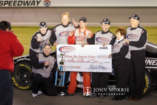 Winning team with a big check in front of a stock car at the Las Vegas Motor Speedway.