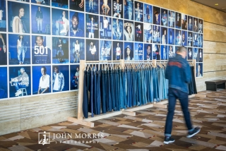 Execute in denim walking past corporate signage and denim apparel.