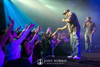 Concerts goers, bathed in blue stage light, reaching out to Ton Loc as he performs on stage.
