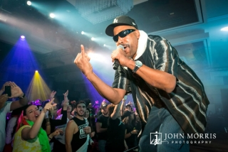 Ton Loc performing on stage for an energetic corporate event crowd.