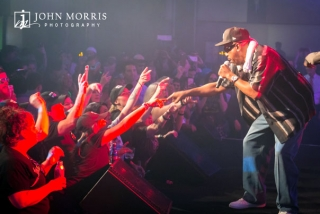 Tone Loc performing on stage and interacting with attendees during a corporate networking event.