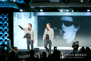 Company executive on stage with his twin in a light hearted moment during a conference keynote.