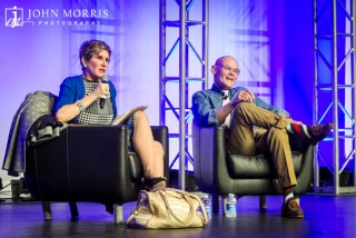 A serious Mary Matalin and jovial James Carville addressing a conference crowd