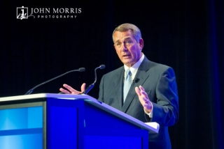 Expressive House Speaker John Boehner on stage speaking during a conference.