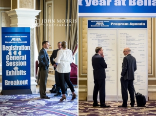 Groups of professionals networking and sharing ideas in front of registration and agenda signage during a corporate event