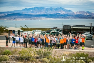 Large group of runners posing after running a corporate sponsored 5k event a with Lake Mead in the background.