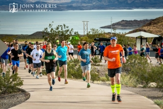 Runners starting out on a corporate sponsored 5k event with beautiful Lake Mead in the background