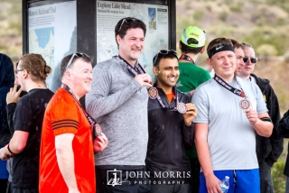 Executive with attendees proudly showing off medals after running a corporate sponsored 5k event
