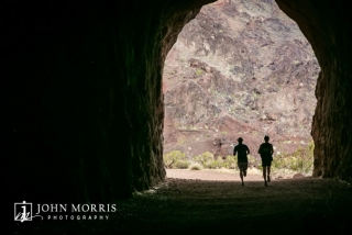Silhouette of two runners entering an old railroad tunnel during an corporate sponsored 5k event.