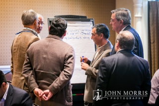 Group of thoughtful attendees gathered around a whiteboard sharing ideas during a breakout session