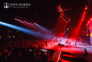 Wide view of band and large crowd bathed in red stage lights performing during a corporate event