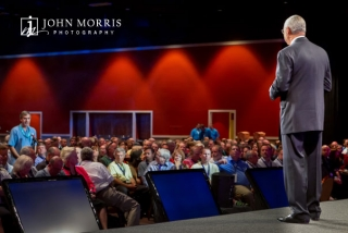 Gen Colin Powell addressing a conference attendee and crowd during a question and answer session