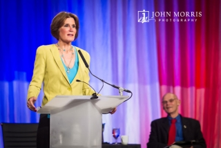 Mary Matalin, on stage addressing a Corporate Event with husband James Carville looking on