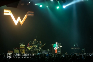 Crowd view of Weezer performing on stage at a corporate event