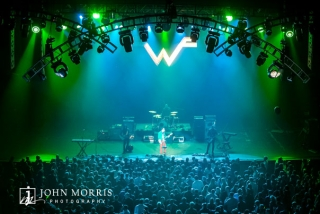 Weezer on stage with enthusiastic crowd at a corporate event