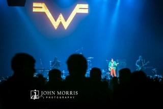 View of Weezer performing on stage from the crowd perspective during a corporate event
