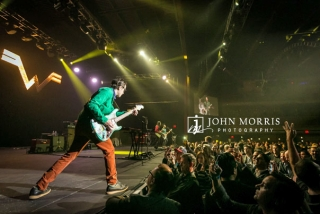 Weezer lead guitarist, on stage and interacting with the crowd during a corporate event
