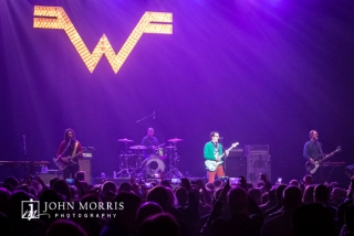 Weezer performing on stage of large crowd during a corporate event