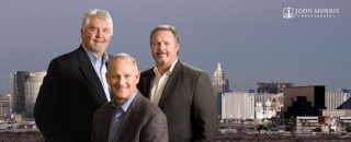 Three corporate executives pose for portrait with the Las Vegas Strip in the background.