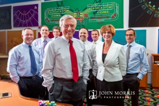 A CEO flanked by his to executives poses in front of roulette table designs his company creates.