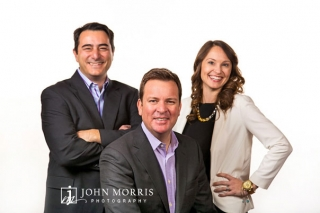 Three executives pose for the camera against a white backdrop in a casual, lifestyle way.