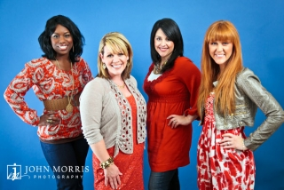 Four members of a women's gospel group smile and pose for the camera in front of a blue background for a publicity photo.