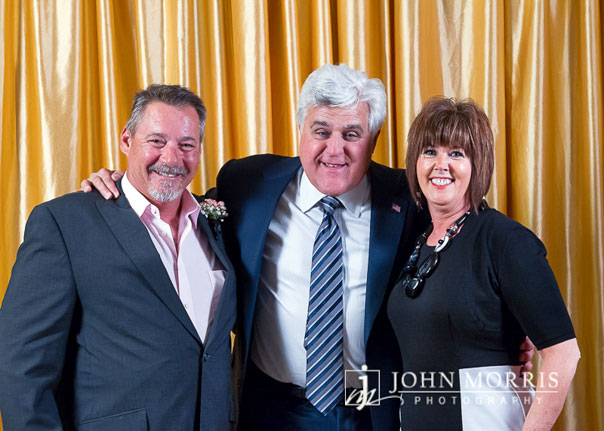 Comedian Jay Leno hugging a couple during a meet & greet in front of a gold backdrop.