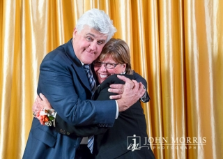 Comedian Jay Leno hugging a fan during a meet & greet in front of a gold backdrop.