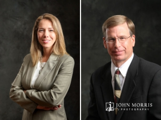 Corporate headshots against a traditional, dark gray background in studio.