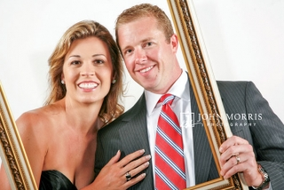 A happy couple poses in front of a white background and behind an empty frame in a photo booth portrait during a corporate event.