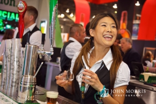 Bartender having a great time at a busy exhibit booth during a trade show.