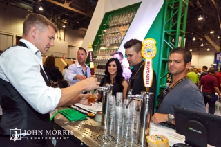 Trade show attendees eagerly wait for the bartender to serve up some beer at an exhibit booth.