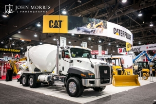 White cement truck on display inside a massive exhibit for Caterpillar construction vehicles inside an exhibit hall for a trade show in Las Vegas.