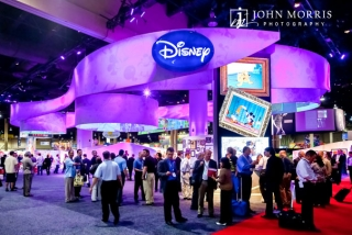 Stunning Disney exhibit booth, full of attendees during a trade show in Las Vegas.