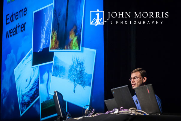 Seated presenter behind a laptop projects a presentation on to a large screen during a breakout session at a corporate event