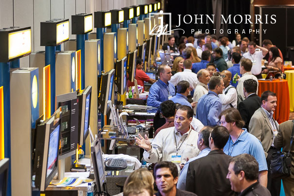 Attendees crowd around exhibits during the trade show portion of a multi day corporate event