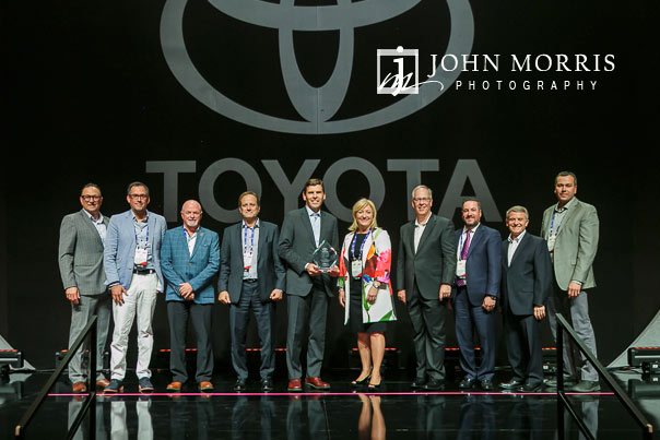 Large group of award winners posing on stage during an awards ceremony during a corporate event at the Mandalay Bay Convention Center in Las Vegas