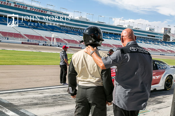 Eager attendee getting last minute instructions before climbing into a race car at the Las Vegas Motor Speedway in Las Vegas as photographed by a San Diego Event Photographer