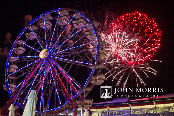Fireworks fill the sky behind a spinning ferris wheel during a corporate event and outing the Las Vegas Motor Speedway in Las Vegas as photographed by a San Diego Event Photographer