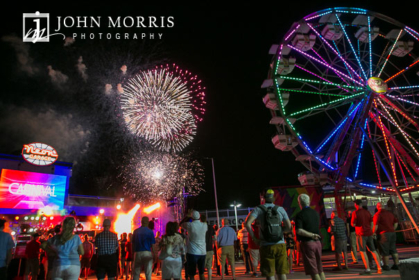 A crowd of attendees look up at the night sky to watch a firework display during a corporate event and outing the Las Vegas Motor Speedway in Las Vegas as photographed by a San Diego Event Photographer