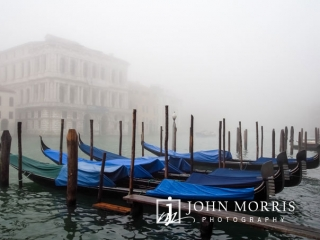 Blue covered Gondolas moored in the early morning foggy hours in Venice canal
