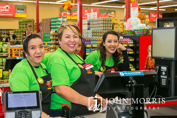 Excited Cashiers getting last minute training during a professional event photographed at a grocery store grand opening in San Diego
