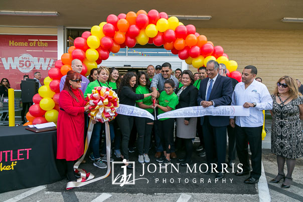The moment a ribbon is cut during a professional event photographed at a grocery store grand opening in San Diego