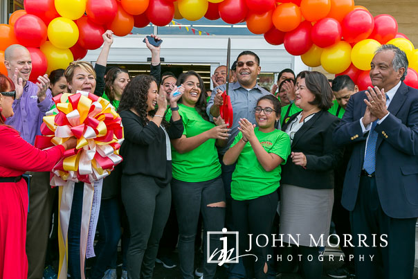 Happy owners and family members after a ribbon cutting during a professional event photographed at a grocery store grand opening in San Diego